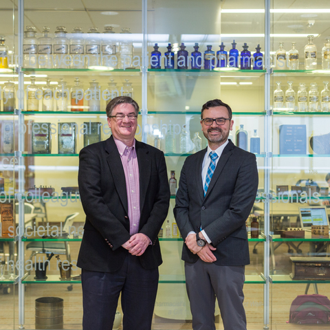 Two people in business suits standing in front of a glass wall.