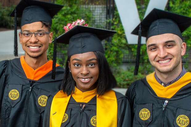 A group of three people in graduation attire, all smiling.