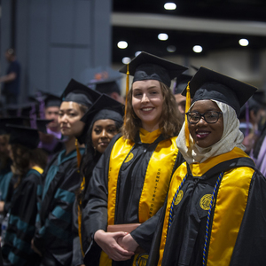 Two VCU graduates stand for a photo at the university's main commencement ceremony May 11 at the Greater Richmond Convention Center.