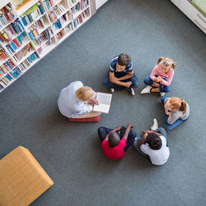 pre-school children and their teacher sitting in a circle in a library