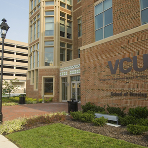 VCU's school of nursing building pictured in foreground with VCU logo and name on side of building facing camera.