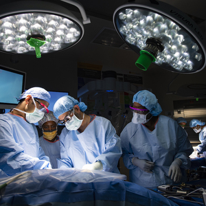 A group of doctors in an operating room performing surgery on a patient.