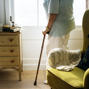 A person holding a cane standing in a living room inside a house.