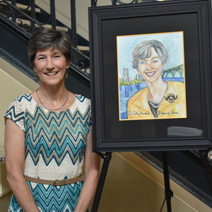 Cathy Howard poses next to a painting of her likeness.