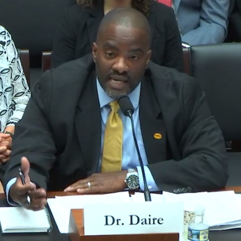 Daire sitting behind desk, speaking to U.S. House of Representatives