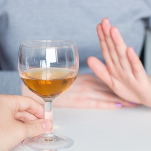 A raised hand to an offered glass of wine implies the refusal of the drink.