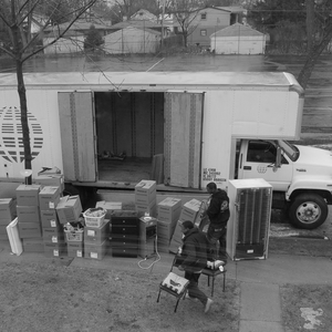 A moving van with its side door open is parked on a street. Various household items and moving boxes sit alongside it. Two moving assistants are putting items next to the van.