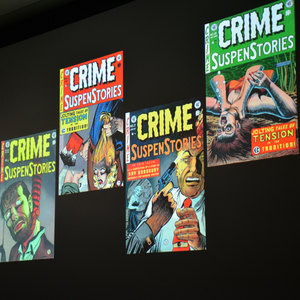 Four covers of editions of Crime SuspenStories are displayed on a screen during a presentation.