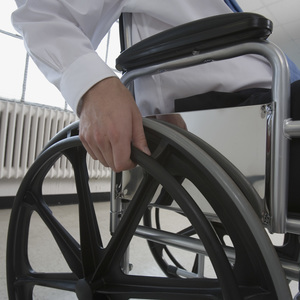A person seated in a wheelchair grapples a wheel.
