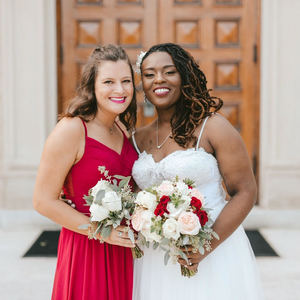 A bride and a bridesmaid standing in front of a church.