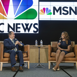 Tim Bajkiewicz, Ph.D., Chandelis Duster seated on a stage. Logos for NBC News and MSNBC are displayed on the screen behind.